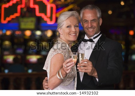 Mature couple celebrating with champagne in casino - stock photo