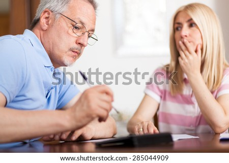 Mature couple checking finances while looking at bills - stock photo