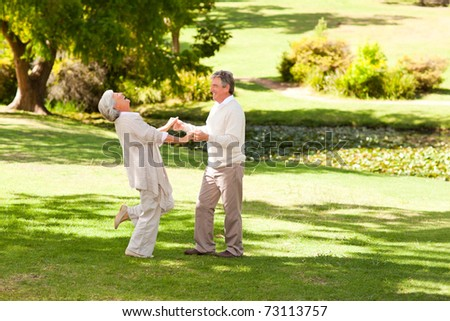Mature couple dancing in the park - stock photo