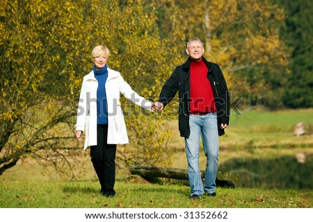 Mature couple deeply in love having a walk holding each other's hand - stock photo