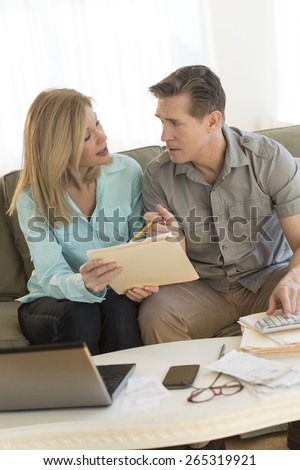 Mature couple discussing while calculating finances on sofa at home