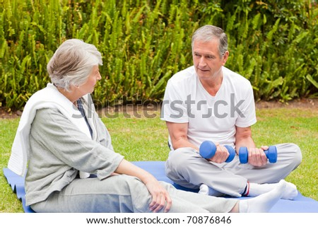 Mature couple doing their exercises in the garden