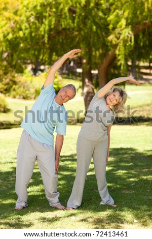 Mature couple doing their streches in the park - stock photo