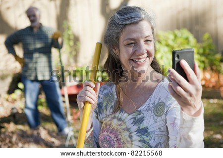Mature couple doing yard work and on the cell phone - stock photo