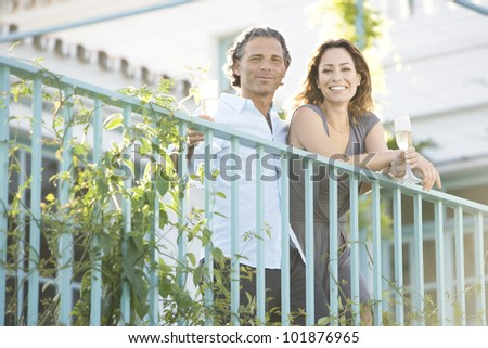 Mature couple drinking champagne while leaning on a hotel's balcony outdoors. - stock photo