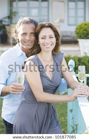 Mature couple drinking champagne while leaning on a hotel's balcony outdoors.