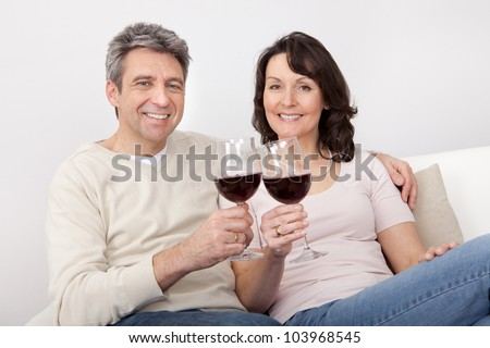 Mature couple drinking red wine at home - stock photo
