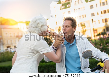 Mature couple eating ice cream. People on city background. Go on vacation in summer. Best time spent together.