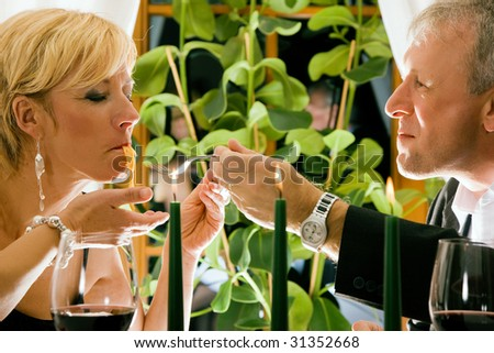 Mature couple eating romantic dinner in a fancy restaurant - stock photo