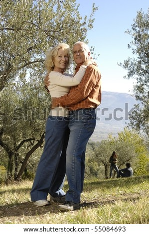 mature couple embracing in the country - stock photo