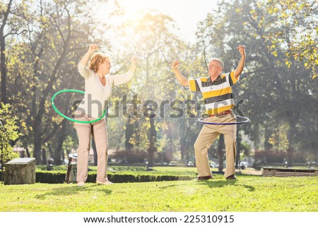 Mature couple exercising with hula hoops in park on a sunny day - stock photo