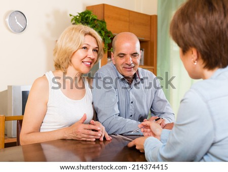 Mature couple filling questionnaire for employee with paper at home - stock photo