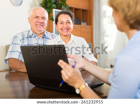 Mature couple filling questionnaire for manager with laptop - stock photo