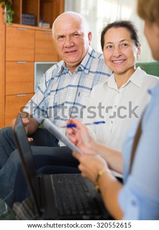 Mature couple filling real questionnaire for employee with laptop of the bank  - stock photo