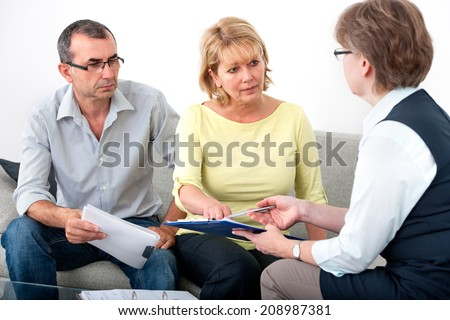 Mature couple getting financial advice from consultant at home - stock photo