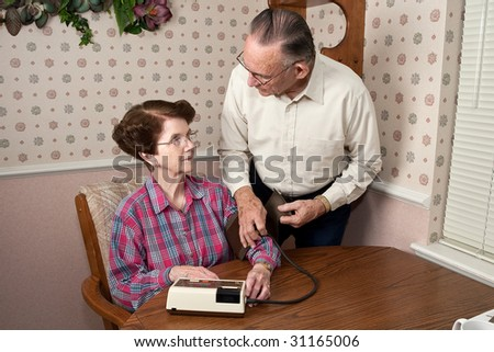 Mature couple getting ready to take blood pressure in home environment.