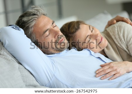 Mature couple having a rest laying down in sofa - stock photo