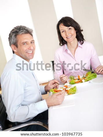 Mature couple having lunch together at home - stock photo