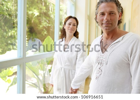 Mature couple holding hands at home, by large glass doors, smiling. - stock photo
