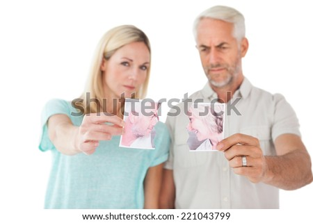 Mature couple holding two halves of torn photograph over white background - stock photo