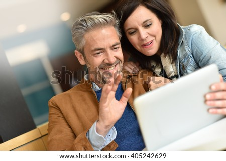 Mature couple in coffee shop connected on internet