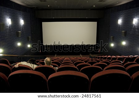Mature couple in empty cinema, with blank silverscreen.