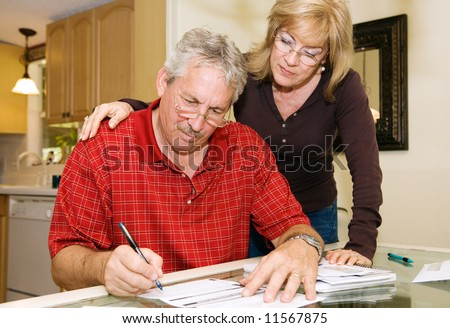 Mature couple in financial trouble is filling out a loan application. - stock photo