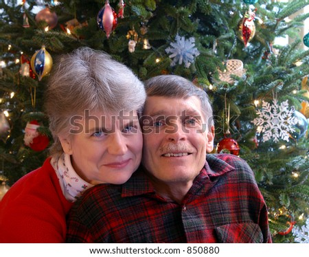 Mature Couple in Front of Christmas Tree
