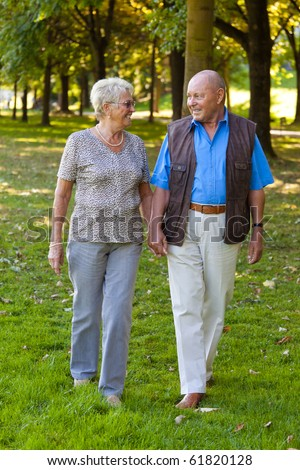 Mature couple in love seniors is walking in a park. - stock photo