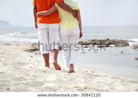 mature couple  in love walking along the beach - stock photo