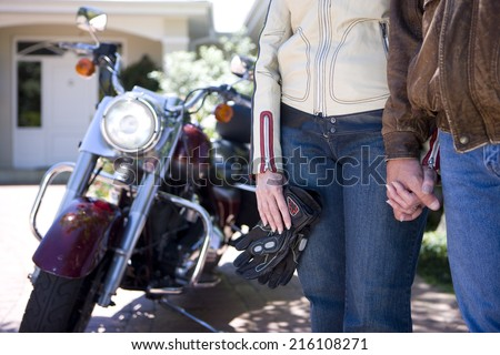 Mature couple in motorcycle gear holding hands - stock photo