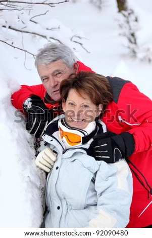 Mature couple in the snow - stock photo