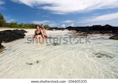 mature couple is sitting together on a white sand beach, tropical beach in Mauritius - stock photo