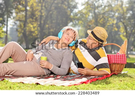 Mature couple listening music and relaxing on a picnic in park on a sunny day  - stock photo