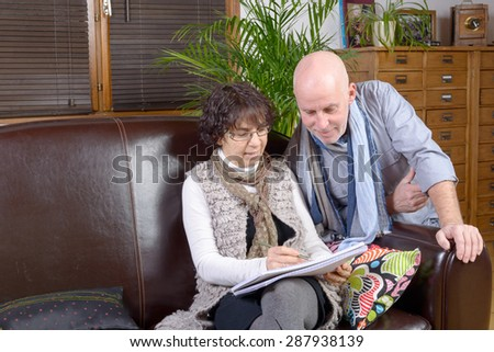 mature couple looking at a note book  in their sofa