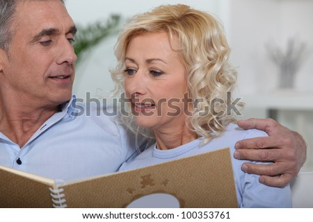 Mature couple looking at a photo album - stock photo