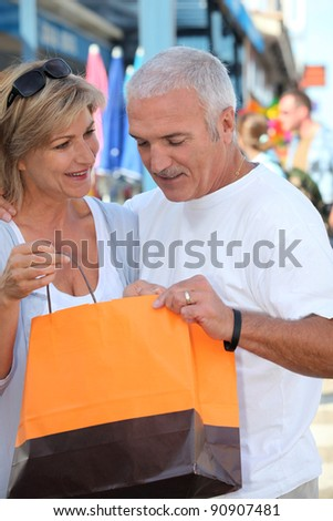 Mature couple looking at a store purchase - stock photo
