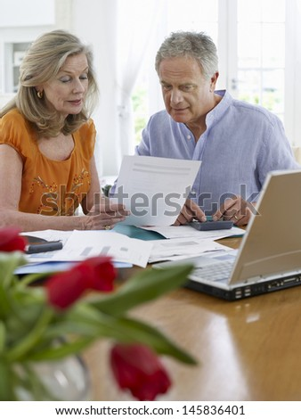 Mature couple looking at bills with calculator and laptop - stock photo