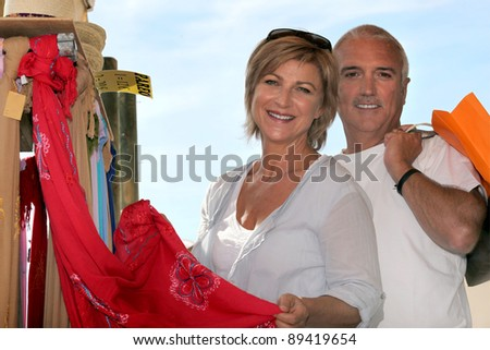 Mature couple looking at sarongs in a holiday shop - stock photo