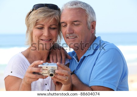 Mature couple looking at the photos on their digital camera - stock photo