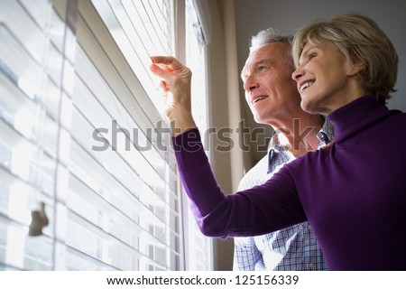 Mature couple looking through blinds - stock photo