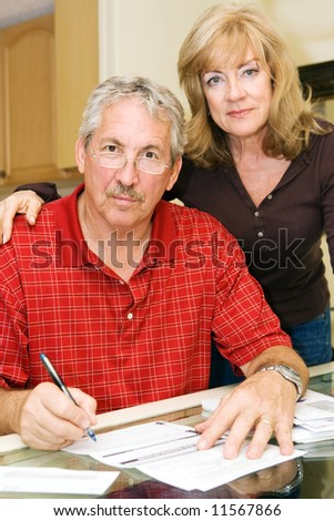 Mature couple looking worried as they try to pay the bills.  Focus on the husband. - stock photo