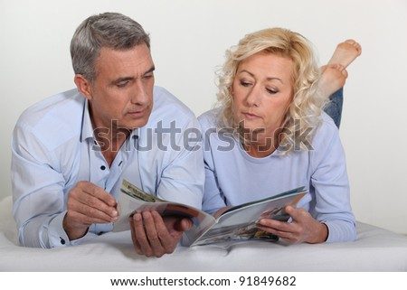Mature couple lying in bed - stock photo