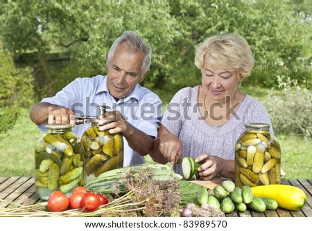 Mature couple making home made pickles - stock photo