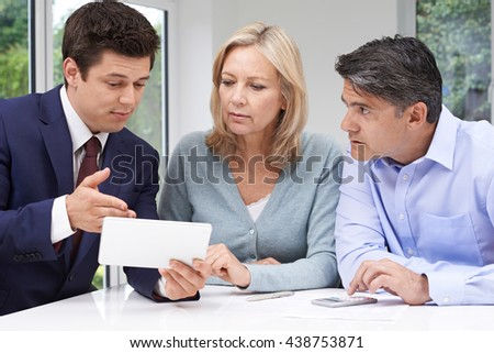 Mature Couple Meeting With Financial Advisor At Home - stock photo