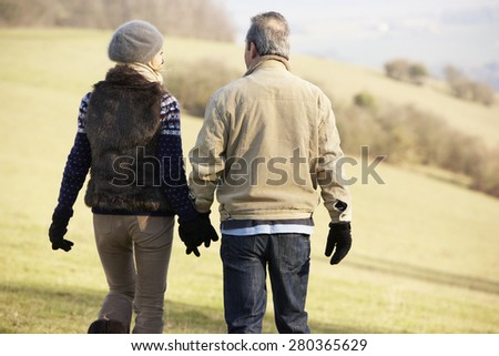 Mature couple on country walk in winter - stock photo
