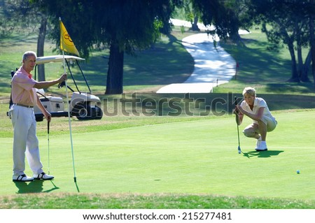 Mature couple playing golf, woman lining up golf shot on putting green, man holding flag - stock photo