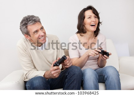 Mature couple playing videogames at home in the couch - stock photo