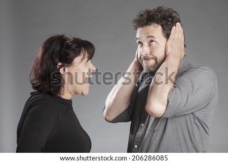 Mature couple quarreling woman shouting man covering ears - stock photo