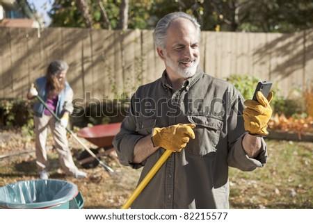 Mature couple raking autumn leaves and using a smart phone - stock photo